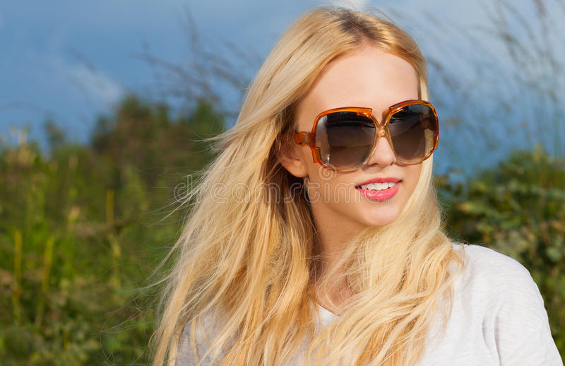 Mulher loura nova bonita elegante em óculos de sol que do vintage seu cabelo fluiu na brisa em uma noite morna do verão foto de stock royalty free