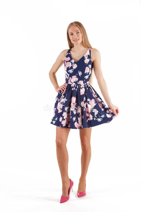 Mulher loura nova bonita em escuro - vestido azul com a c?pia floral isolada no fundo branco imagens de stock royalty free
