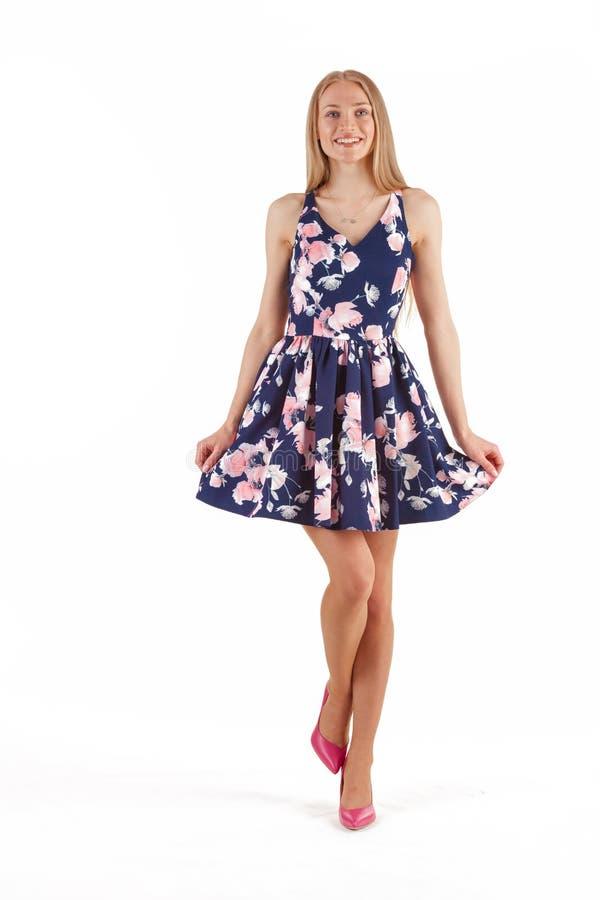 Mulher loura nova bonita em escuro - vestido azul com a c?pia floral isolada no fundo branco imagem de stock royalty free