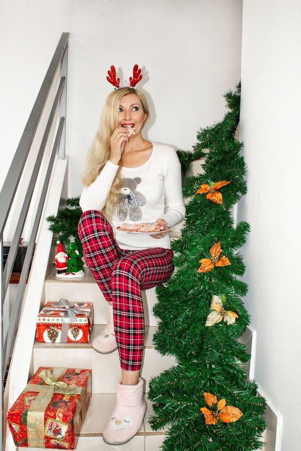 Mulher loura nova bonita em pijamas do Natal e com os chifres da rena, sentando-se nas etapas e mantendo uma cookie decorada imagens de stock royalty free