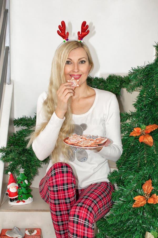 Mulher loura nova bonita em pijamas do Natal e com os chifres da rena, sentando-se nas etapas e mantendo uma cookie decorada imagens de stock