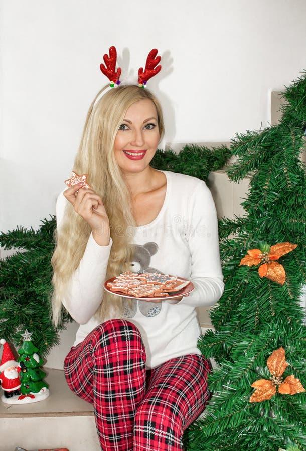 Mulher loura nova bonita em pijamas do Natal e com os chifres da rena, sentando-se nas etapas e mantendo uma cookie decorada fotografia de stock