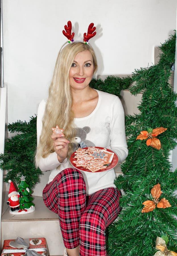 Mulher loura nova bonita em pijamas do Natal e com os chifres da rena, sentando-se nas etapas e mantendo uma cookie decorada foto de stock royalty free