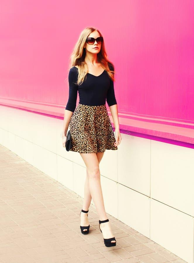 Mulher loura nova bonita na saia e nos óculos de sol do leopardo com embreagem da bolsa que anda na rua da cidade imagem de stock royalty free