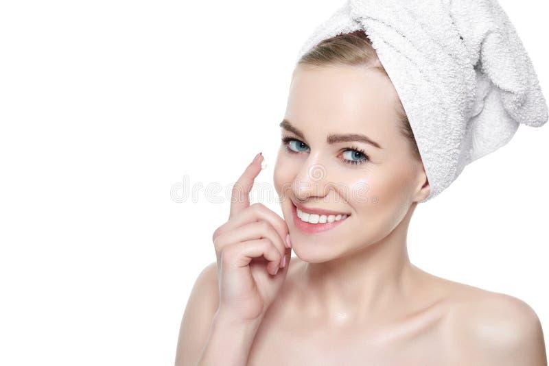 Mulher loura nova bonita que aplica o creme de cara sob seus olhos Tratamento facial imagem de stock royalty free