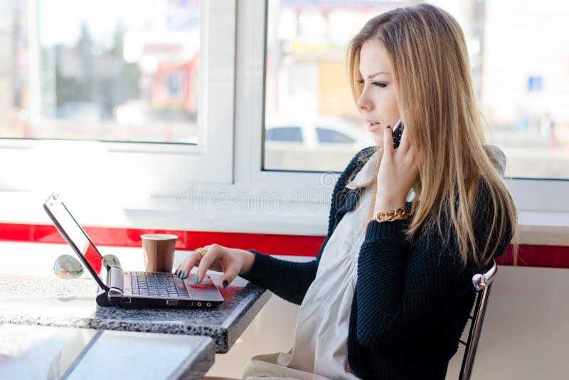 Mulher loura nova bonita séria da mulher de negócio que fala no telefone celular móvel que trabalha em um computador do PC do por imagens de stock royalty free