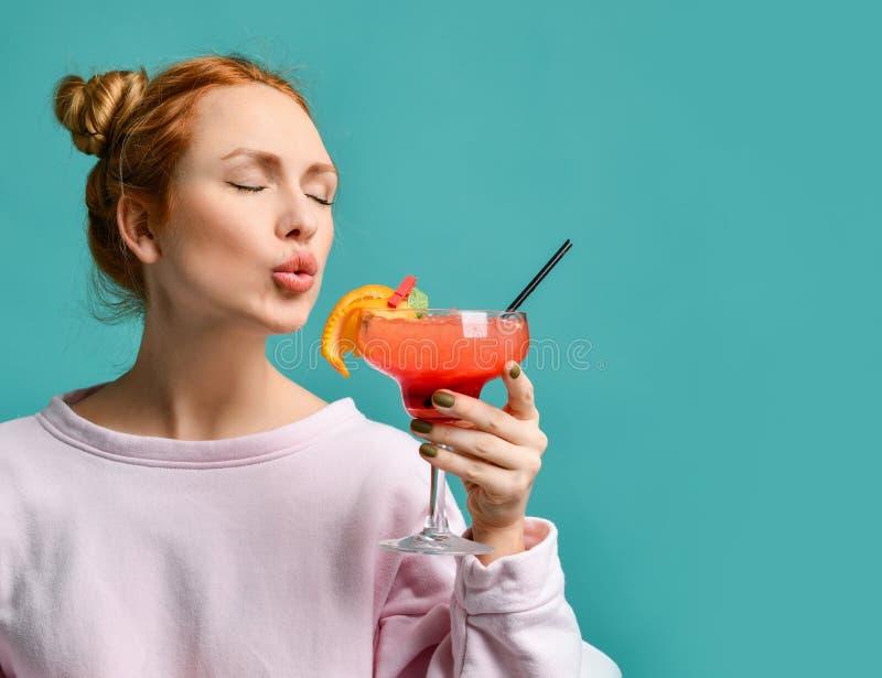 Mulher loura nova com cabelos no bolo e nos olhos fechados que vão tentar um cocktail do margarita da morango imagens de stock