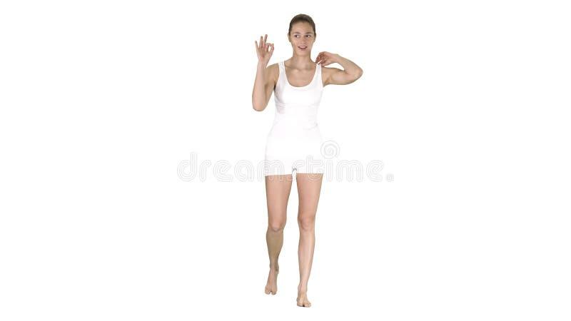 Mulher loura nova com cara feliz que sorri fazendo o sinal da aprova??o no fundo branco imagem de stock
