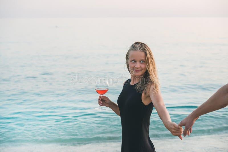 Mulher loura nova com o vidro do vinho cor-de-rosa que guarda a mão do homem na praia pelo mar no por do sol Alanya, Turquia imagem de stock