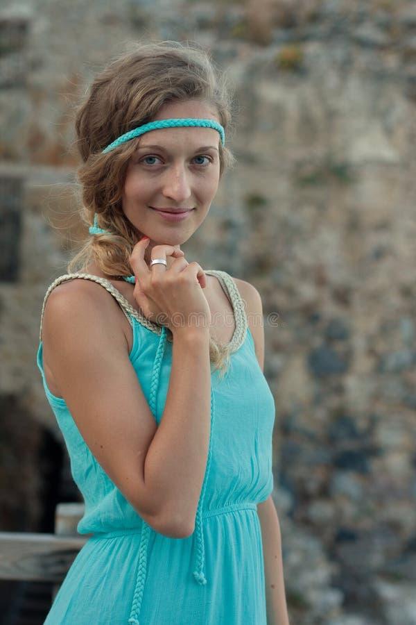 A mulher loura nova com olhos azuis e trançada ouve o turq vestindo foto de stock