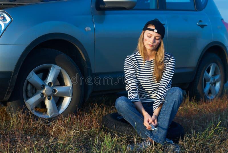 Mulher loura nova com seu carro quebrado foto de stock royalty free