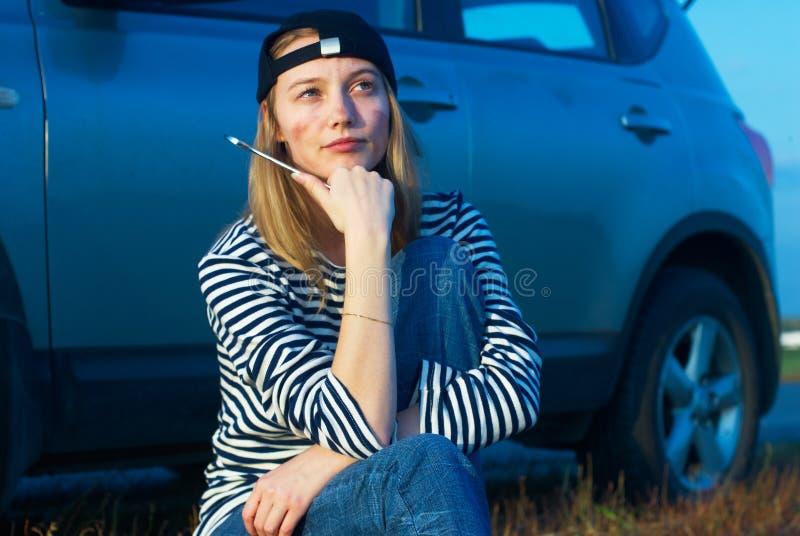 Mulher loura nova com seu carro quebrado imagens de stock