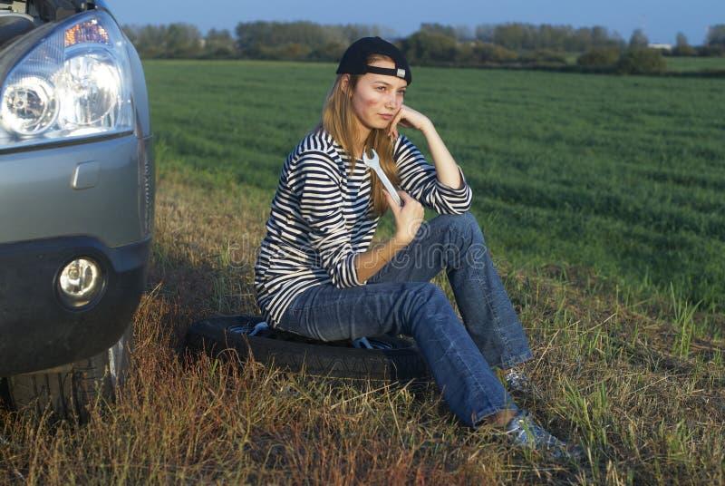 Mulher loura nova com seu carro quebrado fotografia de stock royalty free