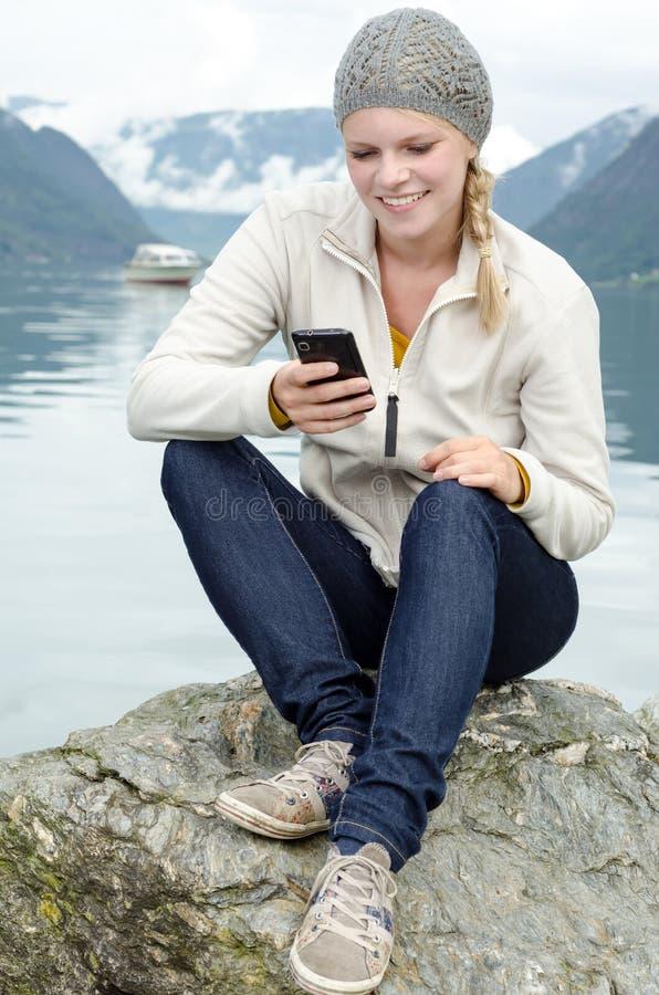 Mulher loura nova com seu Smartphone na mão fotografia de stock royalty free