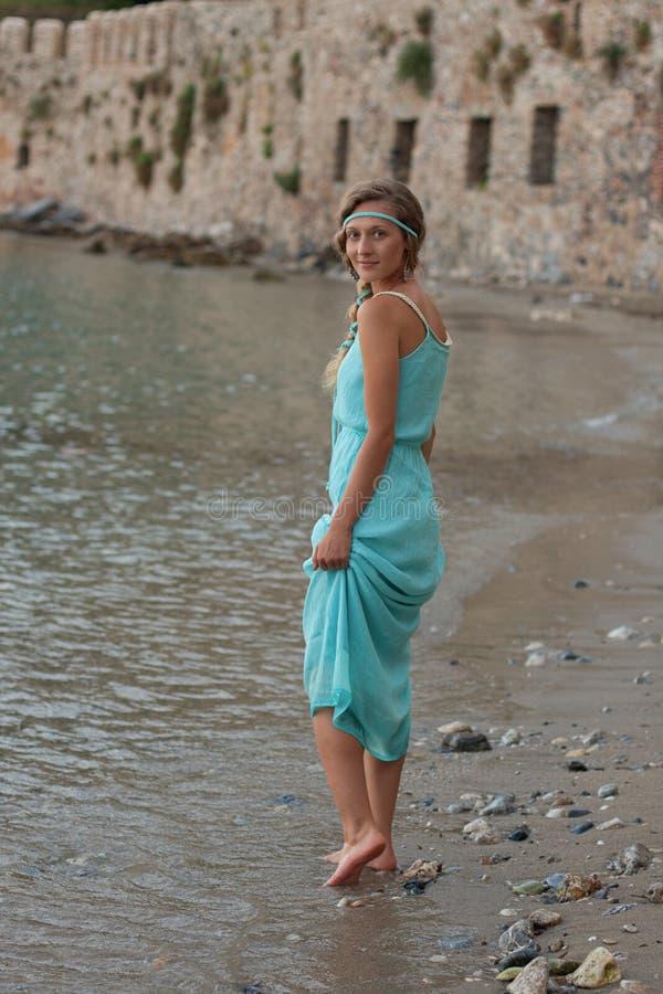 A mulher loura nova com trançado ouve o passeio vestindo de turquesa imagens de stock
