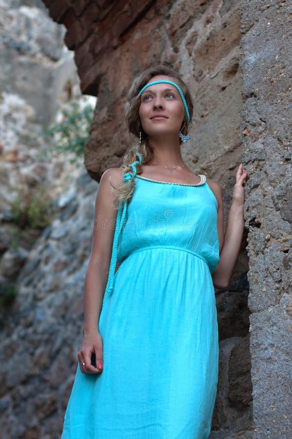 A mulher loura nova com trançado ouve o vestido vestindo de turquesa fotografia de stock royalty free