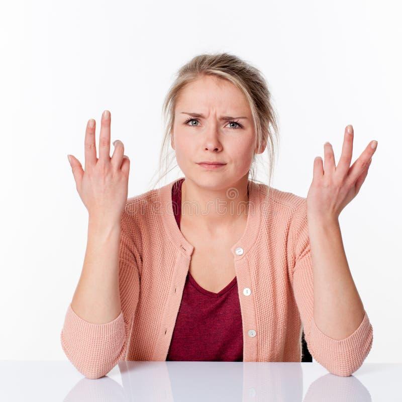 Mulher loura nova de queixa que expressa-se com mãos irritadas acima foto de stock royalty free
