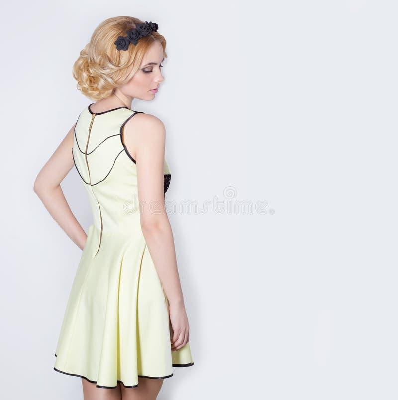 Mulher loura nova elegante delicada bonita bonita em um vestido amarelo do verão com a grinalda da flor do pricheskoyi em seu cab imagem de stock royalty free