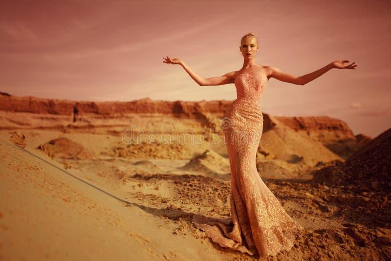 Mulher loura nova elegante no deserto no suporte longo do vestido do ouro com mãos abertas, durante no fundo do por do sol imagem de stock