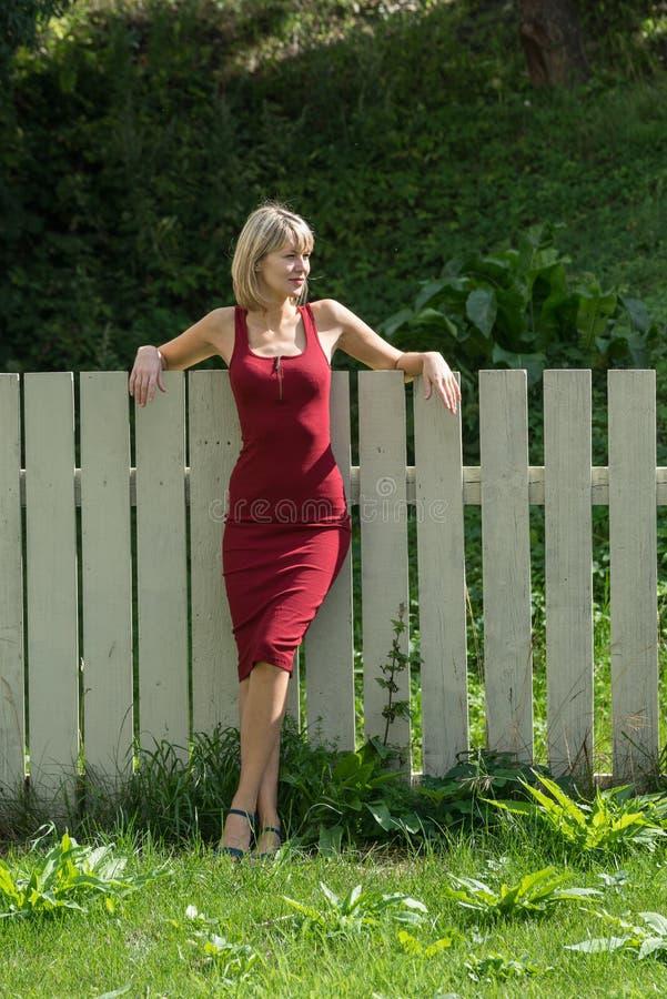 Mulher loura nova em um vestido vermelho que inclina-se contra a cerca de madeira fotografia de stock royalty free