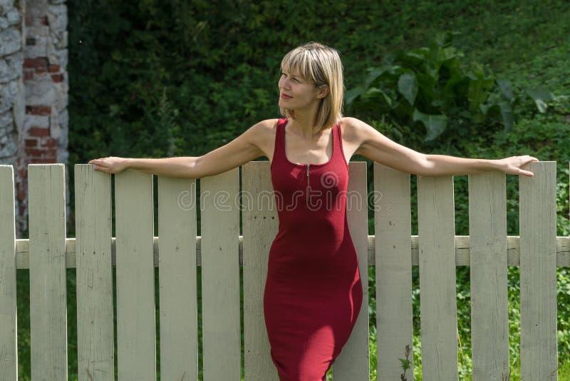 Mulher loura nova em um vestido vermelho que inclina-se contra a cerca de madeira imagens de stock