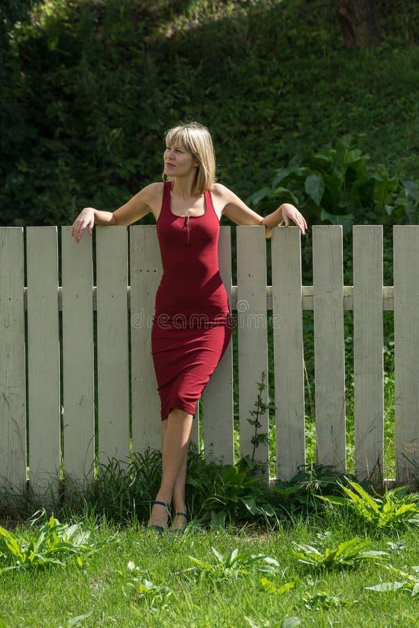 Mulher loura nova em um vestido vermelho que inclina-se contra a cerca de madeira fotos de stock