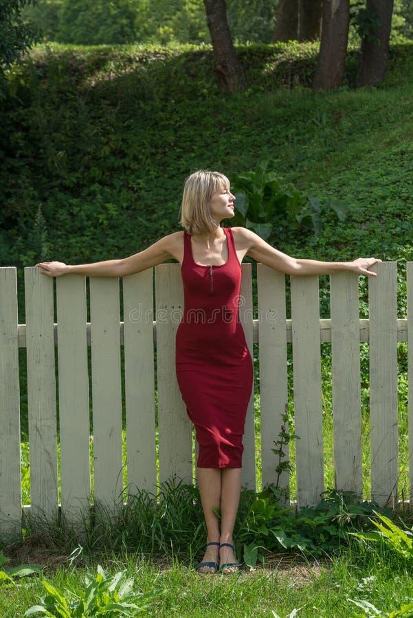 Mulher loura nova em um vestido vermelho que inclina-se contra a cerca de madeira fotografia de stock