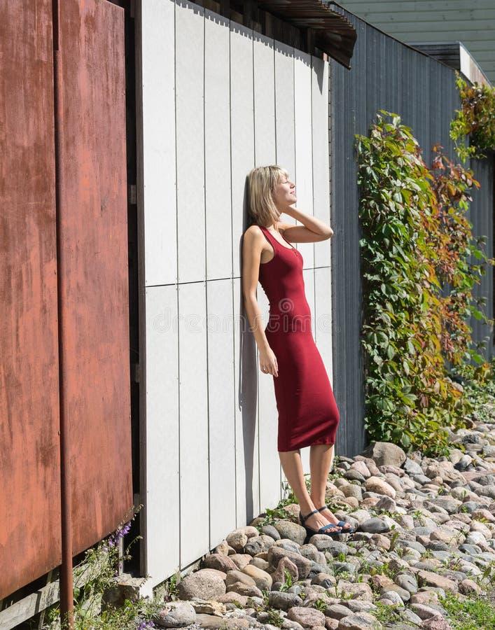Mulher loura nova em um vestido vermelho que inclina-se contra a parede de madeira fotografia de stock royalty free