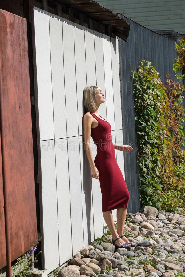 Mulher loura nova em um vestido vermelho que inclina-se contra a parede de madeira fotos de stock
