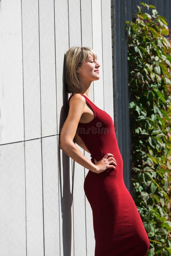 Mulher loura nova em um vestido vermelho que inclina-se contra a parede de madeira imagens de stock