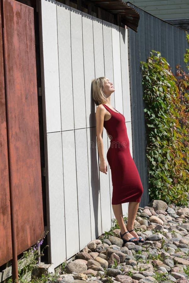 Mulher loura nova em um vestido vermelho que inclina-se contra a parede de madeira imagem de stock royalty free