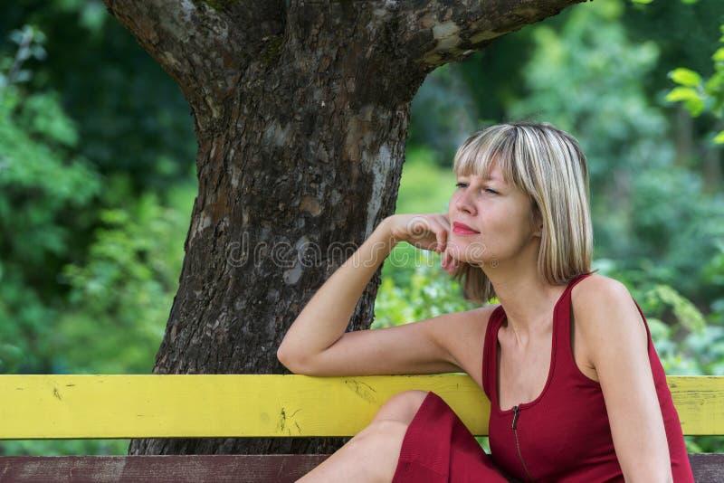 A mulher loura nova em uma inclinação vermelha do vestido senta-se em um banco de madeira foto de stock royalty free