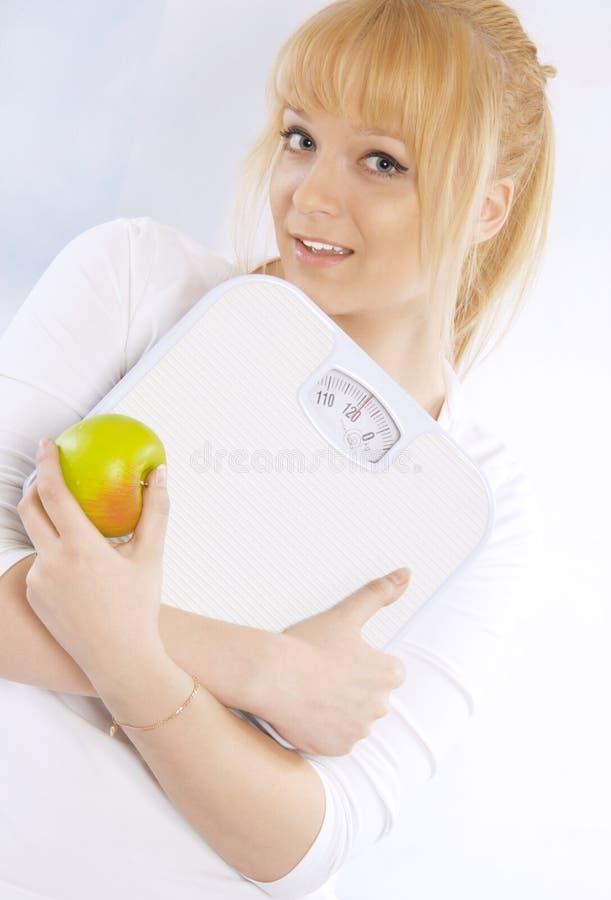Mulher loura nova feliz com uma maçã e as escalas fotos de stock royalty free
