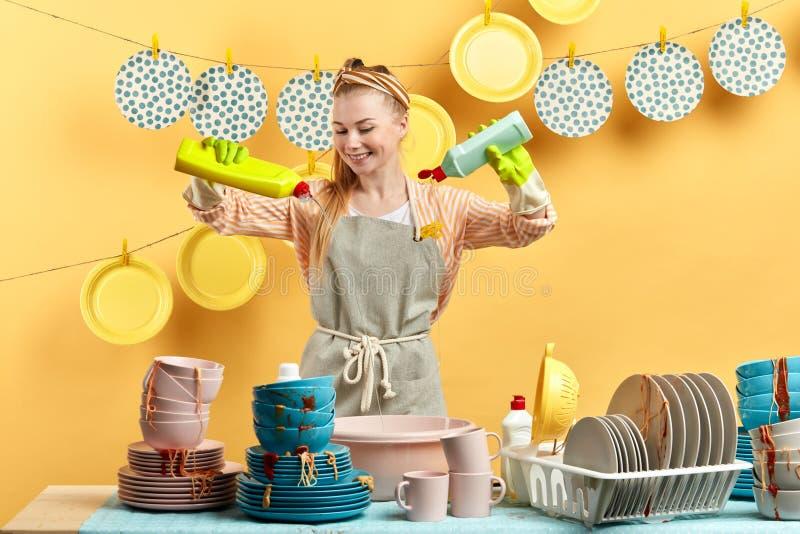 Mulher loura nova feliz entusiasmado que faz trabalhos domésticos foto de stock royalty free