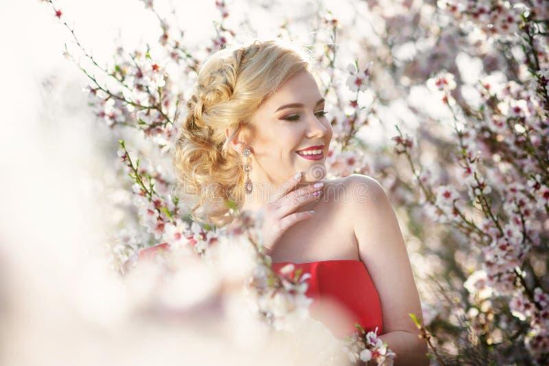 Mulher loura nova feliz no retrato do estilo de vida do jardim de flores da mola foto de stock royalty free
