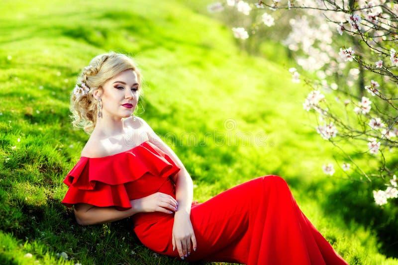 Mulher loura nova feliz no retrato do estilo de vida do jardim de flores da mola imagem de stock
