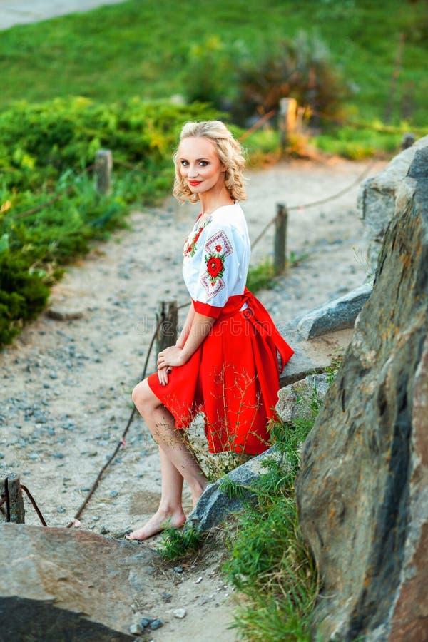 Mulher loura nova feliz shoeless atrativa no vestido branco vermelho ? moda que levanta no trajeto no monte estar na vila da estr fotografia de stock