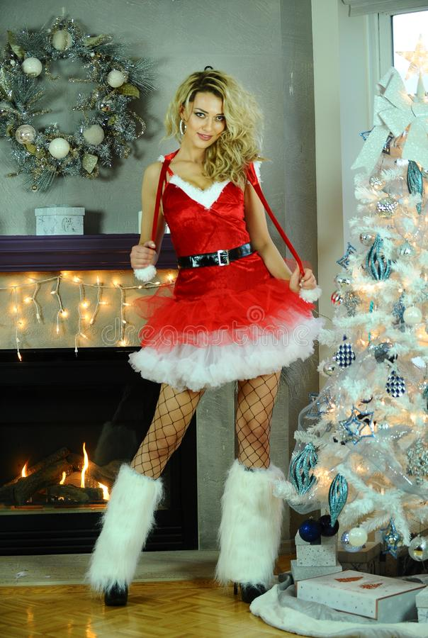 A mulher loura nova flirty lindo vestida como o ajudante 'sexy' de Santa que levanta consideravelmente no Natal decorou o interio fotografia de stock royalty free