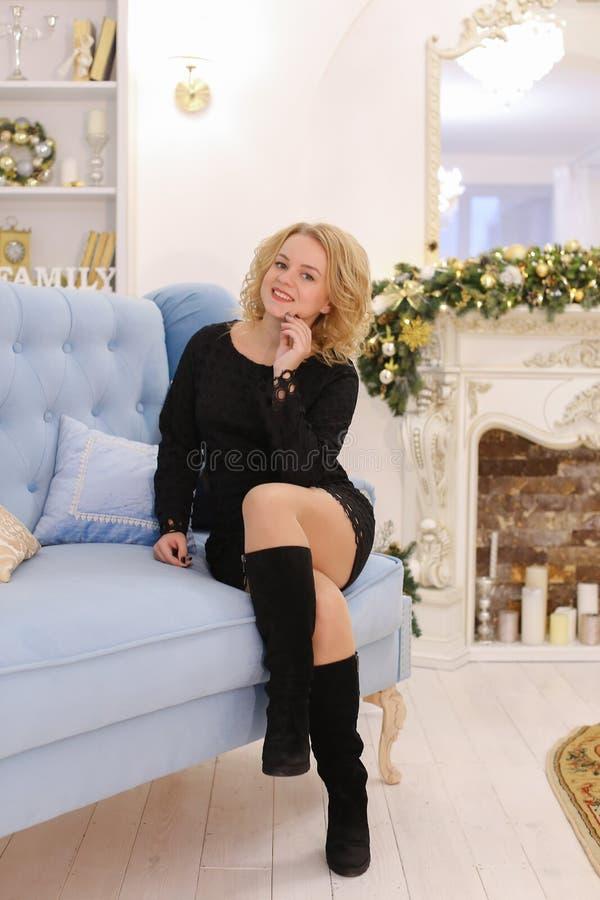 Mulher loura nova maravilhosa que sorri e que levanta o assento no sofá foto de stock