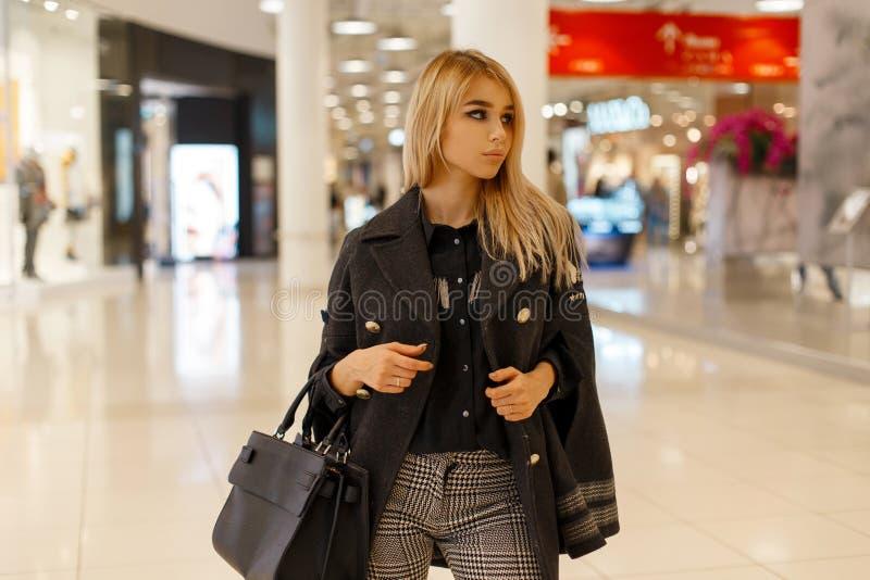 Mulher loura nova moderna em um revestimento na moda do outono com um lenço morno do vintage com uma bolsa preta de couro da form imagens de stock royalty free