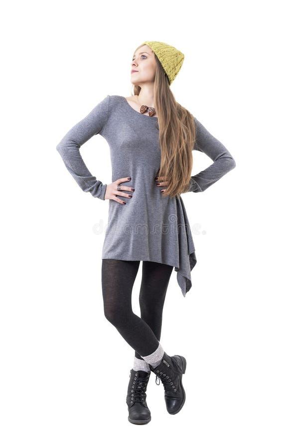 Mulher loura nova na forma autêntica que veste o tampão amarelo do beanie e a túnica cinzenta que olham acima imagens de stock royalty free