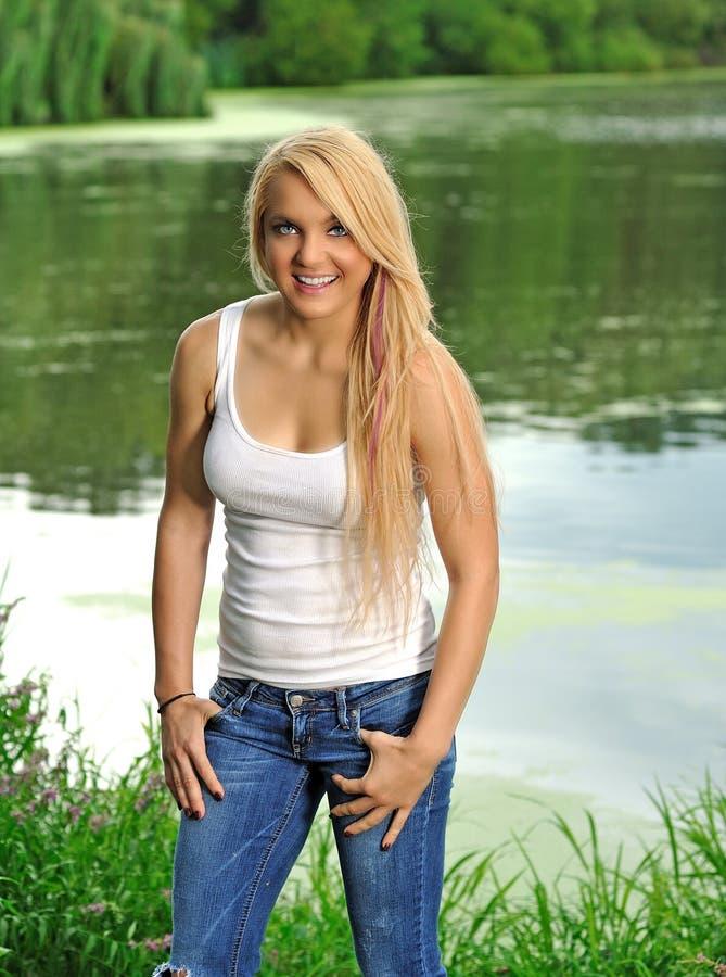 Mulher loura nova na parte superior e nas calças de brim brancas de tanque fotos de stock