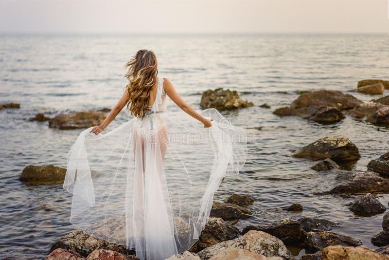 Mulher loura nova na posição branca do vestido do verão nas rochas e em olhar o mar A menina caucasiano aprecia a vista bonita no imagem de stock royalty free