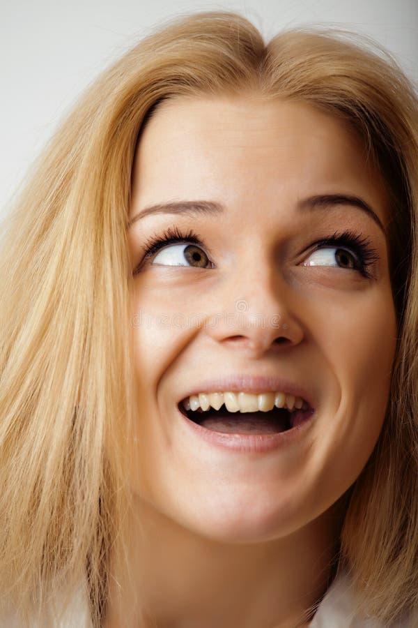 Mulher loura nova no backgroung branco que sorri, fim de levantamento emocional isolado acima, conceito dos povos do estilo de vi imagem de stock royalty free