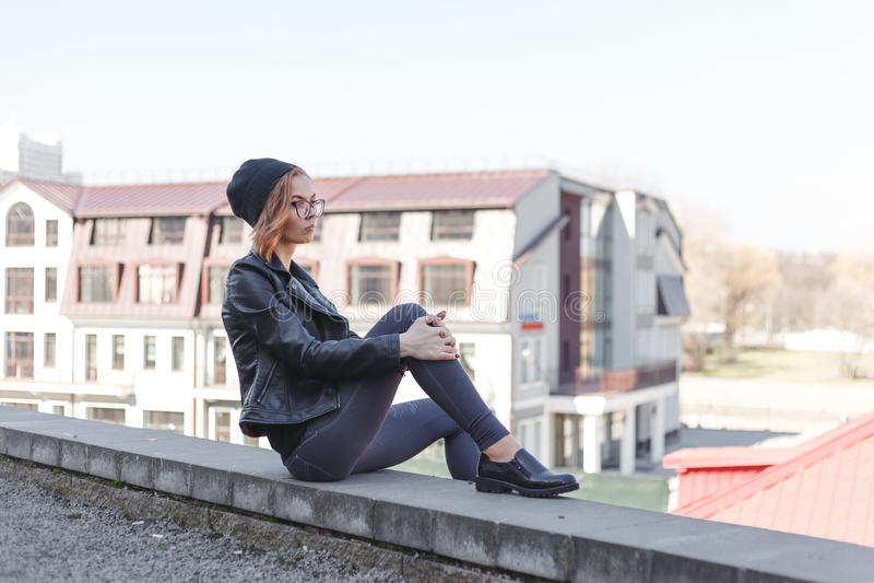 A mulher loura nova no preto relaxa na borda do telhado no centro da cidade imagens de stock royalty free