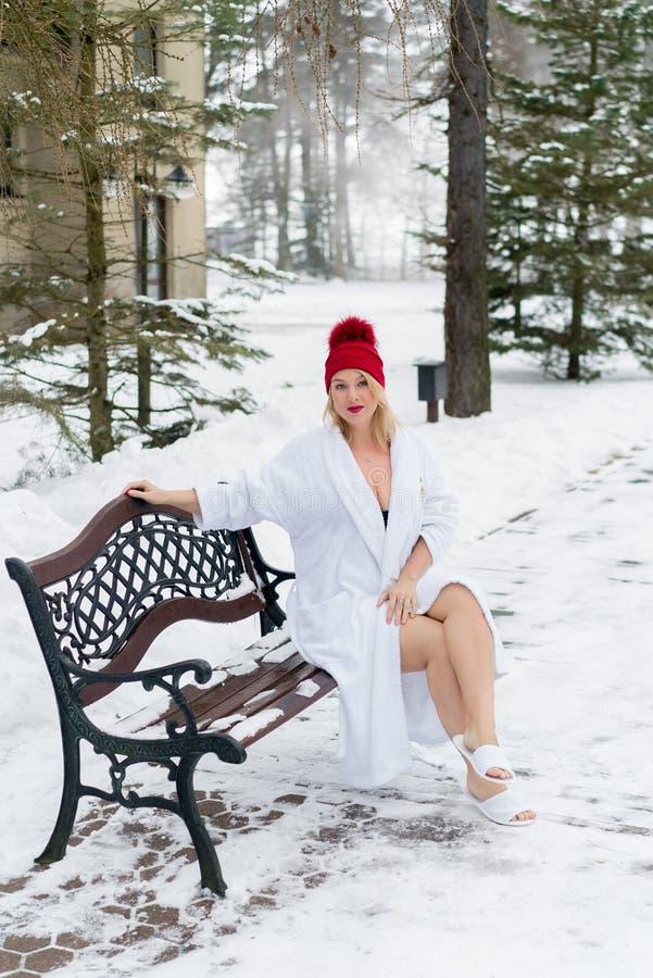 Mulher loura nova no roupão e na cabana vermelha que sentam-se no banco no inverno fora fotos de stock royalty free