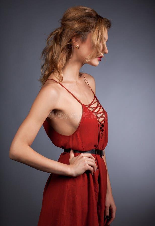 Mulher loura nova no vestido vermelho no fundo cinzento imagem de stock royalty free