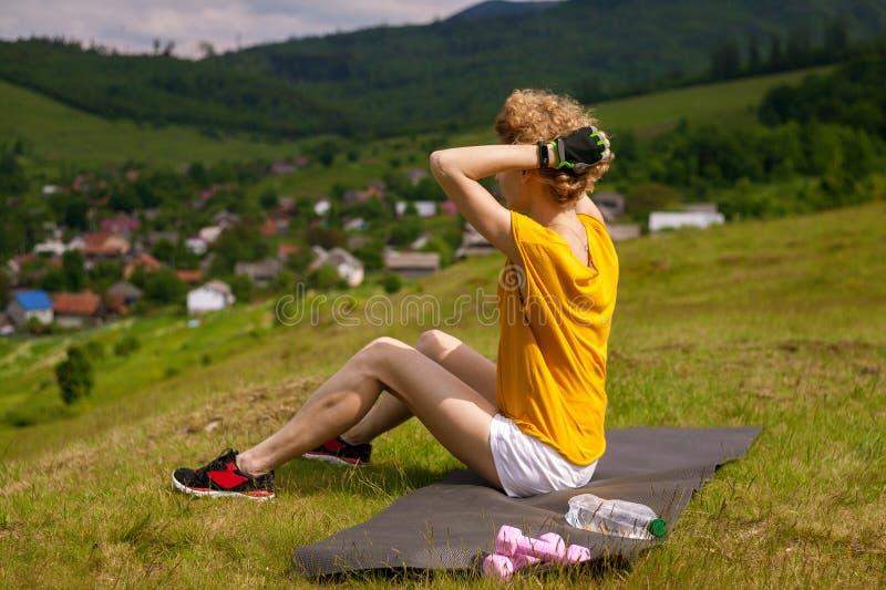 Mulher loura nova para fazer exercícios da ioga no auge do monte no nascer do sol Conceito do estilo de vida fotografia de stock royalty free