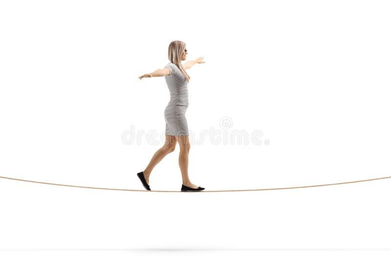 Mulher loura nova que anda em uma corda com propagação dos braços fotografia de stock