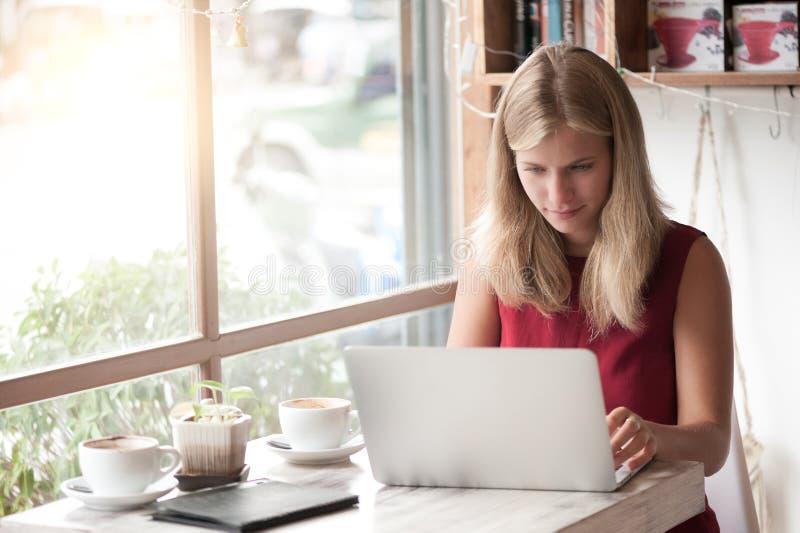 Mulher loura nova que datilografa no portátil no café fotos de stock royalty free
